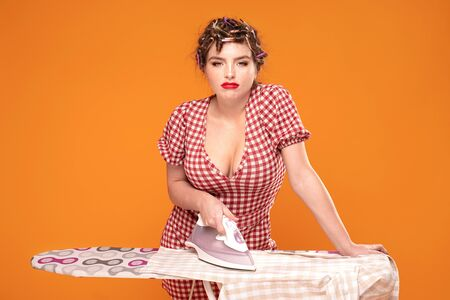 Sad beautiful housewife during ironing clothes. Pinup girl with rollers on head and glamour makeup. Zdjęcie Seryjne