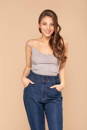 Jonge moderne vrouw in trendy kleding. Bruin haar, spijkerbroek. Mode lookbook. Stockfoto