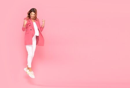 Cheerful young crazy woman jumping over pastel pink background in studio. People lifestyle concept.