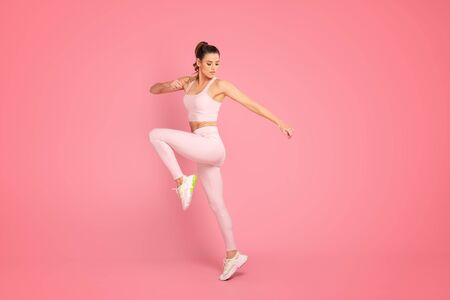 Fitness and healthy lifestyle concept. Sporty Woman Jumping Exercising In Studio Over pink pastel Background. Foto de archivo