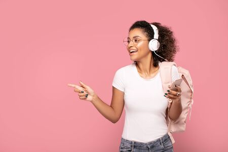 Young african american girl student in casual clothes with backpack and mobile phone isolated on pink pastel studio background. Education in high school university college concept.