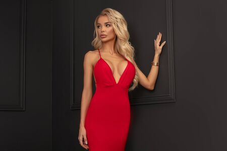 Fashion photo of beautiful sensual woman with blond long hair in red dress. Girl posing in studio on dark wall, looking at camera.