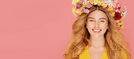 Beauty photo of happy spring lady with beautiful smile. Red hair girl with flowers posing on pastel pink studio background. Human emotions, expression concept.