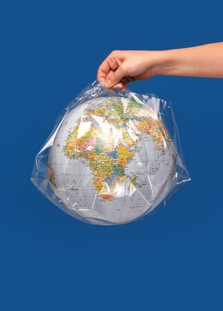 Hand holding a world globe wrapped in plastic. Plastic contamination or protection against the epidemic infectious diseases or the air pollution. Blue studio background.