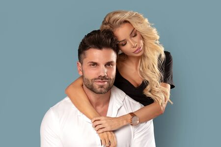 Sensual young couple posing on blue studio background.