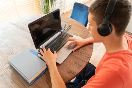 Teenage boy doing homework using computer sitting by desk in room alone.