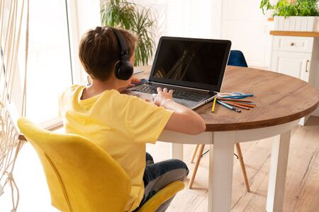 Boy child studying at home using laptop. Distance learning, online lesson, video conference, school lessons in electronic form. Modern school, technology, education, children concept.