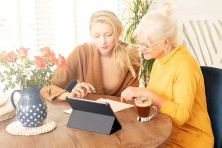 Senior Caucasian woman and her adult daughter spending time together at home, using a tablet.