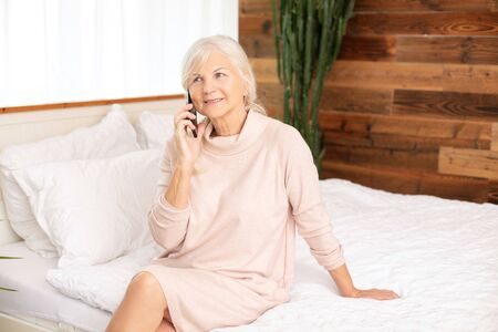 Calm beautiful senior woman sitting on bed and talking by mobile phone. Enjoying free retirement time.
