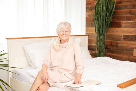 Calm beautiful senior woman sitting on bed with book, relaxing. Enjoying free retirement time. 版權商用圖片 - 148223195