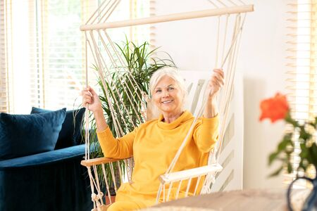 Portrait of beautiful senior woman sitting on a boho swing at home and smiling. Mature lady relaxing in living room. Happy retirement concept.