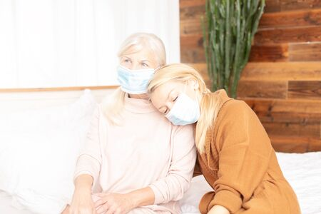 Senior ill woman with caring daughter at home. Quarantine time. Ladies wearing medical masks.