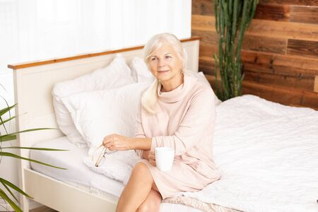 Calm beautiful senior woman sitting on bed with cup of hot tea or coffee, relaxing. Enjoying free retirement time. 版權商用圖片