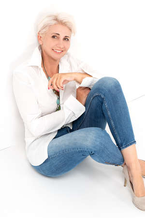 Pretty blonde confident mature woman posing in studio, wearing white shirt and jeans. Lifestyle people concept