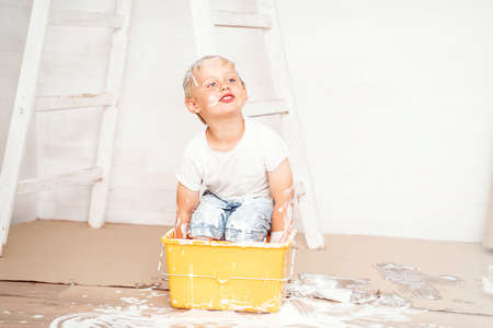 Happy kids painting wall. Home improvement and renovation. Child applying white paint on walls in bedroom. Family moving into new house.