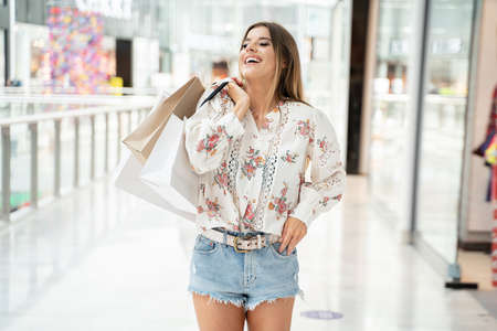 Woman with shopping bags walking in shop, smiling.