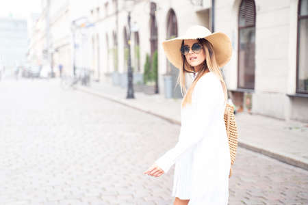 Young beautiful happy woman on vacation wearing summer hat and fashionable sunglasses.