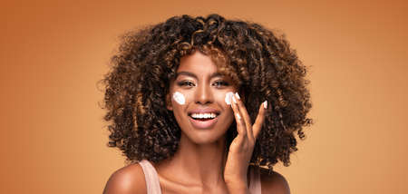 Young afro woman with moisturizer on face. Beautiful african girl applying a cream on cheek. Beauty girl with perfect and healthy skin.