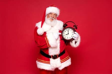 Real jolly Santa Claus holding alarm clock. Christmas time. Red studio background. Banco de Imagens