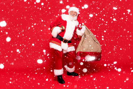 Happy, real, funny Santa Claus holding sack bag with Merry Christmas presents, delivering xmas gifts. Red background, a lot of copy space. Banco de Imagens
