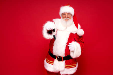 Real jolly Santa Claus holding car keys as a Christmas gift.Red studio background.
