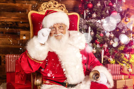 Real Santa Claus with gifts and beautiful Christmas tree. Christmas concept.