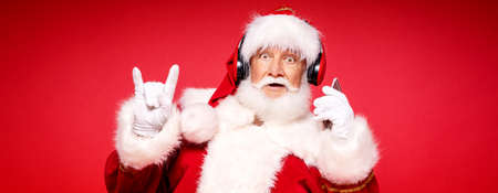 Funny bearded real Santa Claus with headphones listening music from mobile phone. Red studio background. Christmas happy time.