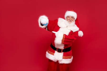 Real jolly Santa Claus holding house keys as a Christmas gift.Red studio background. Banco de Imagens