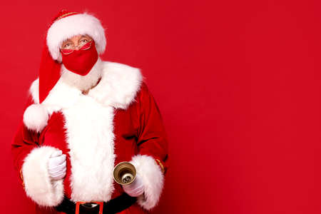 Real Santa Claus in red mask posing over studio background. A lot of copy space.