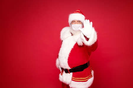 Real Santa Claus in white mask posing over red studio background. A lot of copy space.