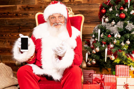 Real Santa Claus showing a mobile phone, sitting near christmas tree and gift boxes. Banco de Imagens
