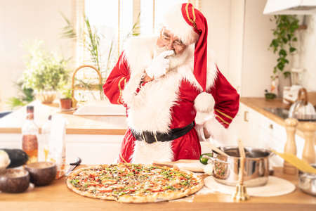 Real Santa Claus making italian pizza in kitchen. Christmas concept.