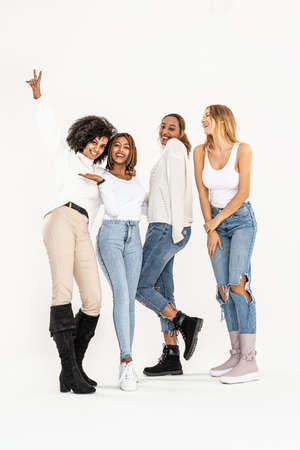 Group of young multi-ethnic attractive girls smiling and having fun together, posing in studio on white background. Friendship and real emotions concept.