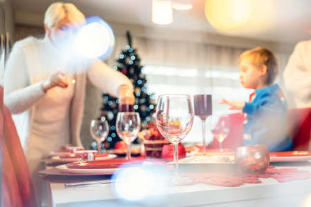 Family preparing xmas dinner. Christmas holidays red table setting concept.