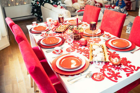 Photo of Christmas holidays red table setting concept. Festive dinner at home.