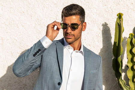 Modern businessman. Confident young man in fashionable suit and sunglasses posing outdoor, relaxing. Handsome guy, elegant style. Influencer.