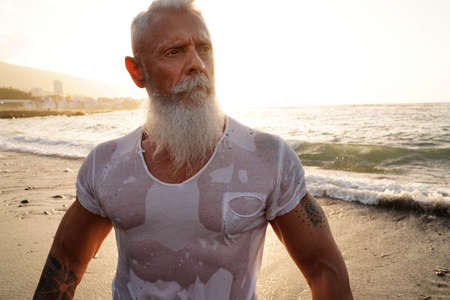 Age is just a number. In a healthy body, healthy mind. Senior man with white stylish beard and muscular fit body with tattoos on the beach. Sunset light. Elderly people healthy lifestyle on a retirement concept.