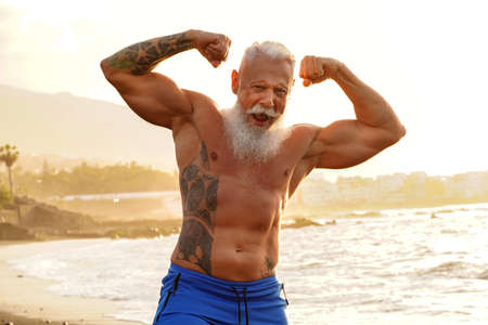 Happy fit senior man showing his muscle on the beach after outdoor workout, during sunset time. In a healthy body healthy mind. Age is just a number. Elderly people lifestyle and real human emotions concept. Banco de Imagens