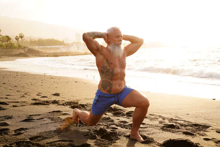 Happy fit senior man exercising on the beach during sunset time. In a healthy body healthy mind. Age is just a number. Elderly people lifestyle and real human emotions concept. Banco de Imagens