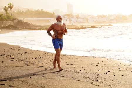 Happy fit senior man running on the beach during sunset time. In a healthy body healthy mind. Age is just a number. Elderly people lifestyle and real human emotions concept.