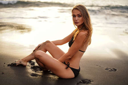 Bikini girl relaxing on the black beach. Young beautiful woman in fashionable swimsuit. Summer vibes. Imagens