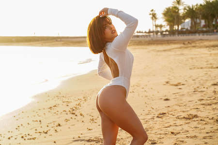 Photo of young woman in white swimwear posing on tropical beach looking at camera. Beautiful latin girl. Sunset time. Summer vacation concept.