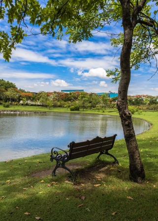 Bench is under the shade of the tree that located near tranquil lake  Bangkok  Thailand  Stock Photo