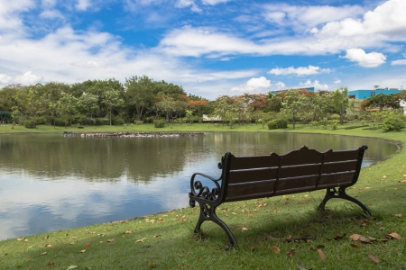The lonely bench in the park with the view of small lake reflection  Bangkok  Thailand  Stock Photo - 14414313