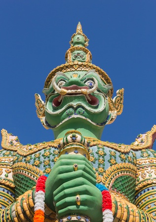 Green guardian statue at the Temple of Dawn was beautifully decorated with tiny pieces of colored ceramics and Chinese porcelain placed delicately into intricate patterns  It is one of Bangkok s world-famous landmarks  Stock Photo