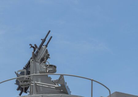 Machine gun on the deck of battleship with the blue sky background  This photo is taken from Battleship memorial at Samuthpraparn Thailand