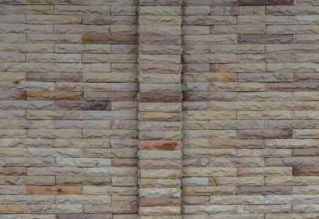 Sand stone bricks wall texture with pole in the middle pattern has shown the variety of natural brown color Stock Photo - 14752496
