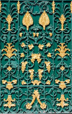 iron bars: Curved steel pattern on green gate with golden flowers, leaves and bunch of grapes texture