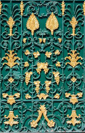 rejas de hierro: Patr�n de acero curvado en puerta verde con flores de oro, hojas y racimos de uvas textura