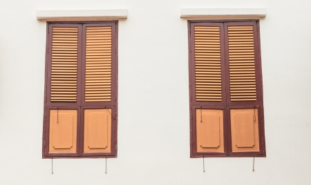 Two old wooden windows on plain concrete wall